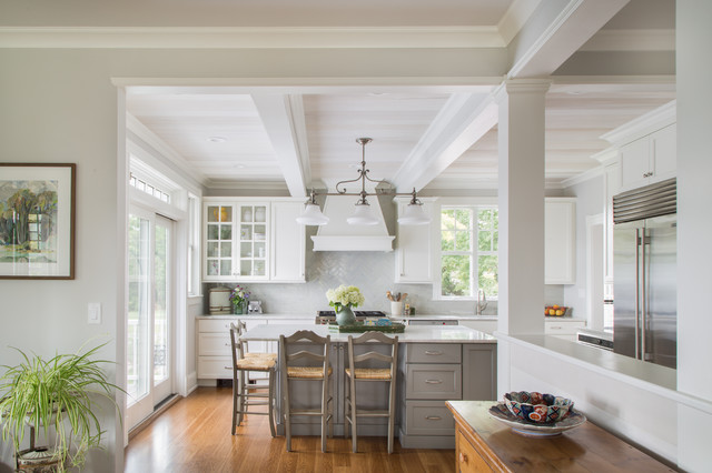 Inspiration for a large nautical l-shaped enclosed kitchen in New York with a belfast sink, recessed-panel cabinets, yellow cabinets, composite countertops, white splashback, ceramic splashback, stainless steel appliances, medium hardwood flooring, a breakfast bar, brown floors and white worktops.