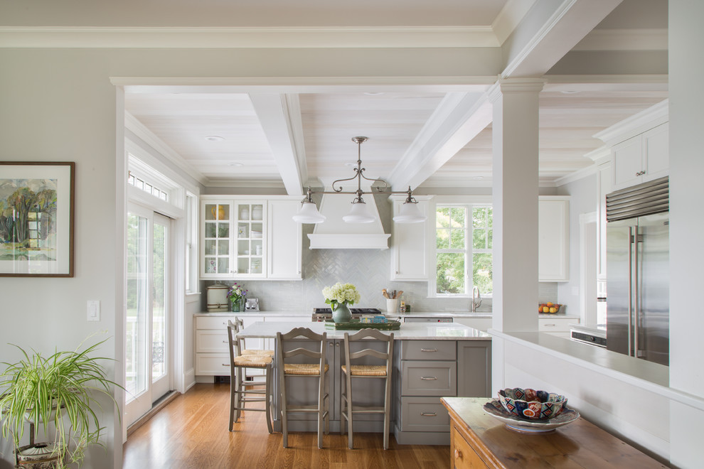 Inspiration for a large coastal l-shaped medium tone wood floor and brown floor enclosed kitchen remodel in Salt Lake City with recessed-panel cabinets, ceramic backsplash, stainless steel appliances, white countertops, an undermount sink, gray cabinets, marble countertops, gray backsplash and an island