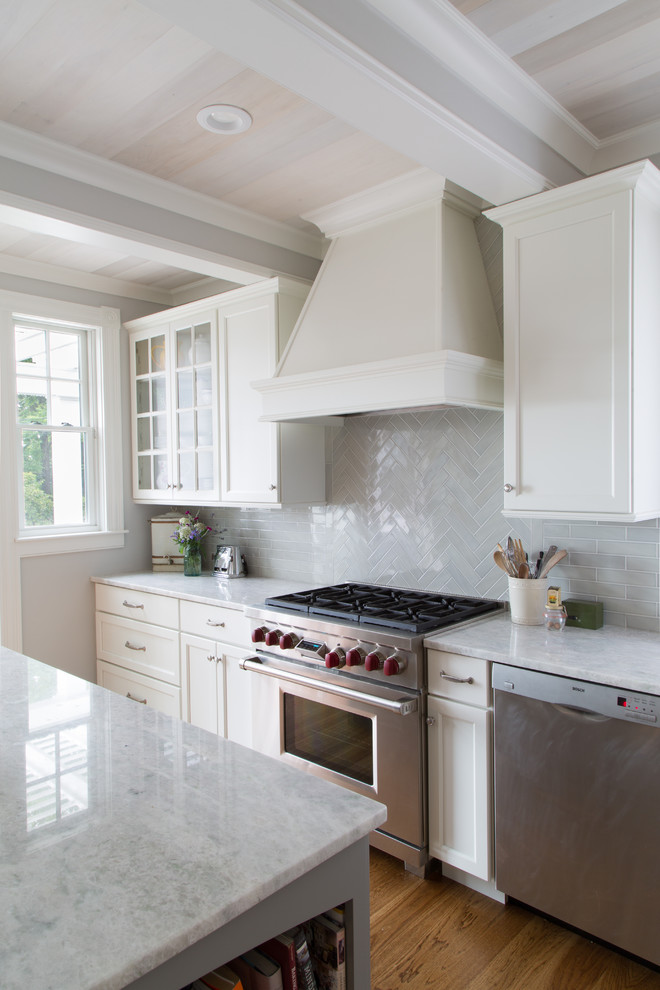 Example of a mid-sized beach style l-shaped medium tone wood floor and brown floor eat-in kitchen design in Salt Lake City with an undermount sink, recessed-panel cabinets, white cabinets, marble countertops, gray backsplash, ceramic backsplash, stainless steel appliances, an island and white countertops