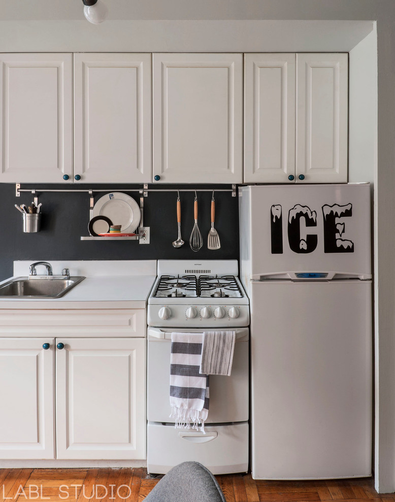 Mid-sized eclectic single-wall eat-in kitchen photo in New York with recessed-panel cabinets, white cabinets and black backsplash