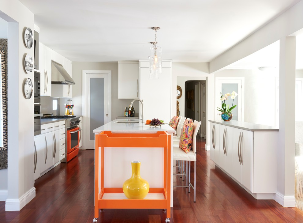 Mid-sized trendy galley brown floor and medium tone wood floor open concept kitchen photo in New York with an undermount sink, flat-panel cabinets, white cabinets, colored appliances, an island and gray backsplash