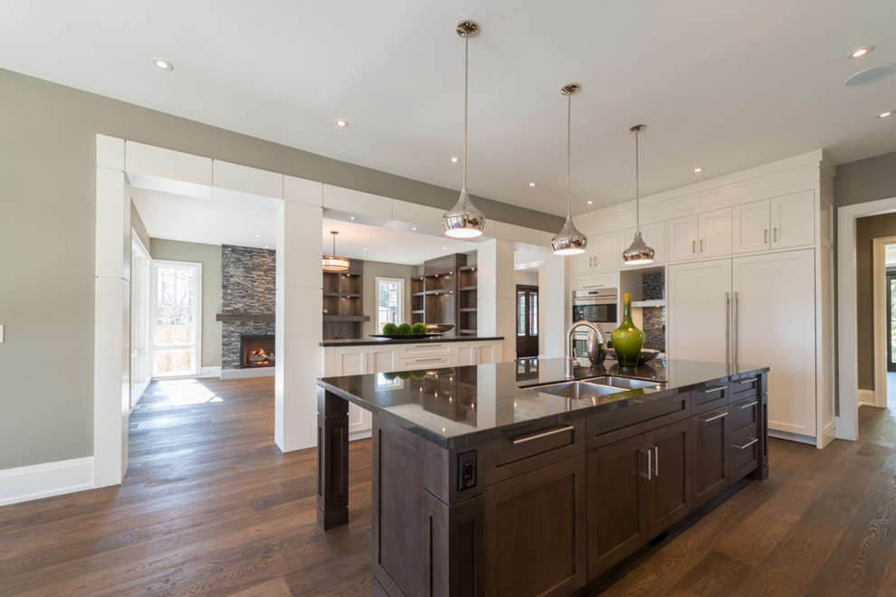 Open concept kitchen - large transitional l-shaped medium tone wood floor open concept kitchen idea in Toronto with an undermount sink, shaker cabinets, white cabinets, granite countertops, black backsplash, mosaic tile backsplash, paneled appliances and an island