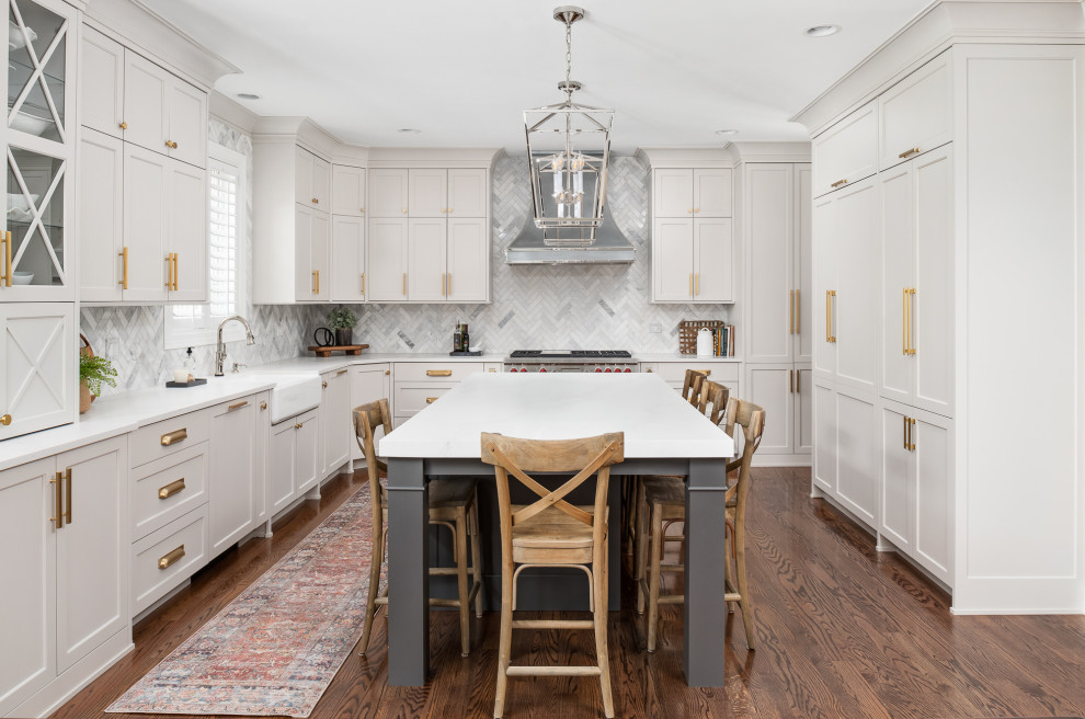 Example of a large transitional u-shaped dark wood floor and brown floor open concept kitchen design in Chicago with a farmhouse sink, recessed-panel cabinets, gray cabinets, quartz countertops, gray backsplash, marble backsplash, stainless steel appliances, an island and white countertops