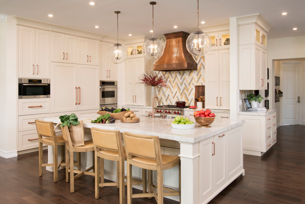 Example of a mid-sized transitional l-shaped medium tone wood floor eat-in kitchen design in Miami with an undermount sink, shaker cabinets, white cabinets, marble countertops, multicolored backsplash and an island