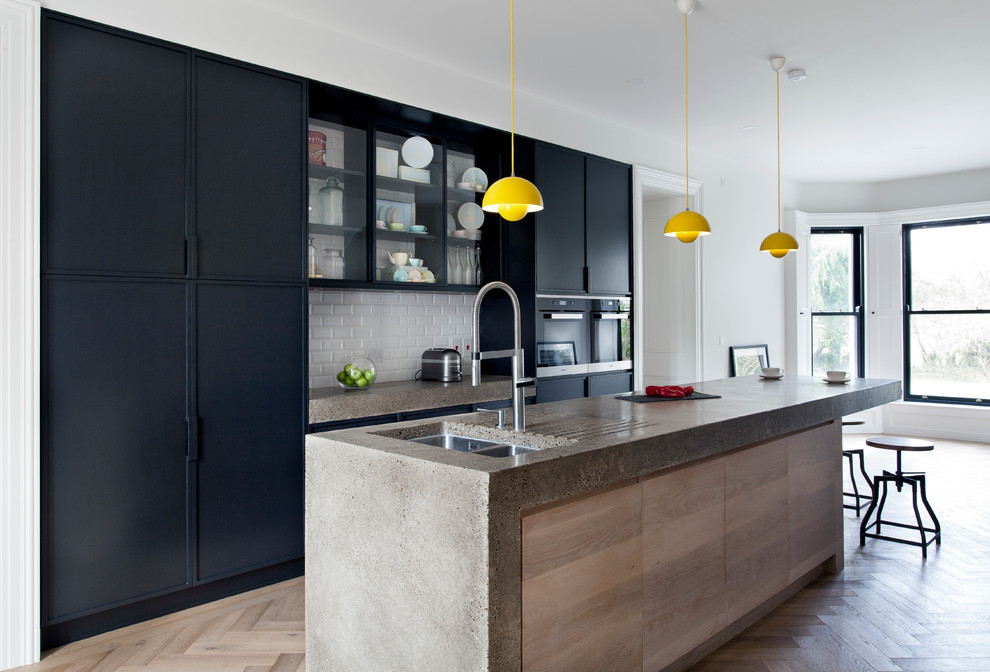 Kitchen - large contemporary light wood floor kitchen idea in Dublin with flat-panel cabinets, black cabinets, concrete countertops, an island, a double-bowl sink, white backsplash, subway tile backsplash and black appliances