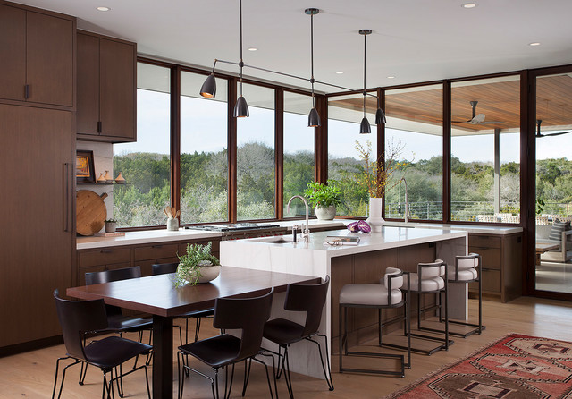 Kitchen - contemporary l-shaped light wood floor and beige floor kitchen idea in Austin with flat-panel cabinets, dark wood cabinets, stainless steel appliances, an island and white countertops