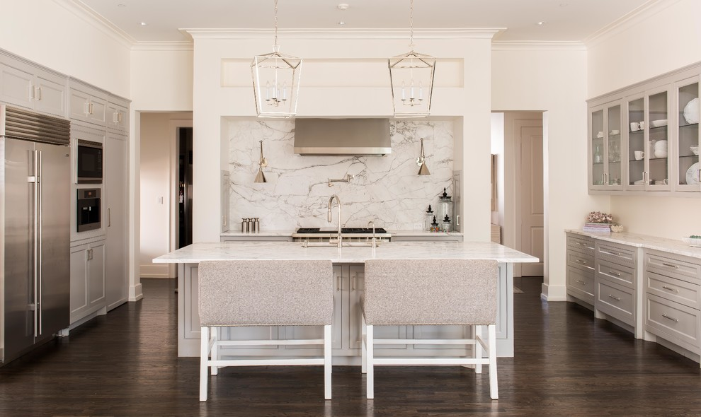 Example of a large transitional u-shaped dark wood floor and brown floor kitchen design in Dallas with recessed-panel cabinets, gray cabinets, marble countertops, stainless steel appliances, an island, an undermount sink, white backsplash and stone slab backsplash