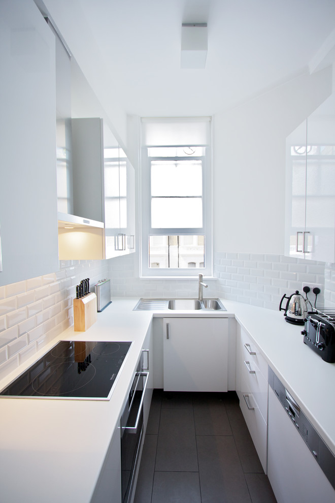 Enclosed kitchen - mid-sized contemporary u-shaped ceramic tile enclosed kitchen idea in London with a double-bowl sink, flat-panel cabinets, white cabinets, laminate countertops, white backsplash, ceramic backsplash, no island and paneled appliances
