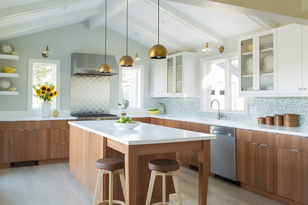 Example of a large minimalist l-shaped light wood floor and brown floor eat-in kitchen design in Salt Lake City with glass-front cabinets, white cabinets, solid surface countertops, multicolored backsplash, mosaic tile backsplash, stainless steel appliances, an island, white countertops and an undermount sink