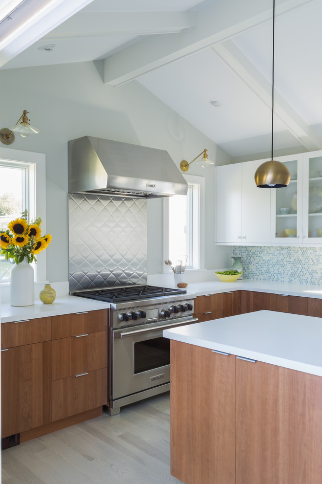 Large minimalist l-shaped light wood floor and brown floor eat-in kitchen photo in Salt Lake City with glass-front cabinets, white cabinets, solid surface countertops, multicolored backsplash, mosaic tile backsplash, stainless steel appliances, an island, white countertops and an undermount sink