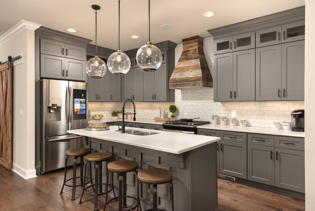 Inspiration for a cottage l-shaped dark wood floor and brown floor kitchen remodel in Other with a double-bowl sink, shaker cabinets, gray cabinets, white backsplash, subway tile backsplash, stainless steel appliances, an island and white countertops