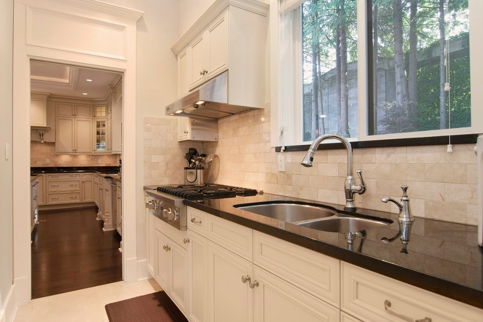 Elegant u-shaped eat-in kitchen photo in Vancouver with an undermount sink, raised-panel cabinets, white cabinets, granite countertops, beige backsplash and stainless steel appliances