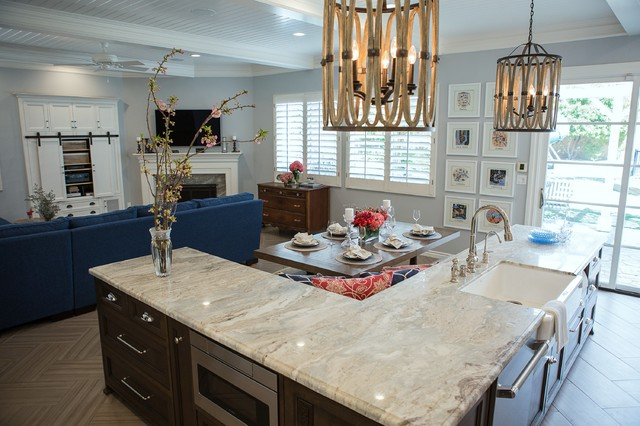 Inspiration for a mid-sized transitional l-shaped ceramic floor and brown floor open concept kitchen remodel in Los Angeles with a farmhouse sink, recessed-panel cabinets, white cabinets, marble countertops, white backsplash, marble backsplash, paneled appliances and an island