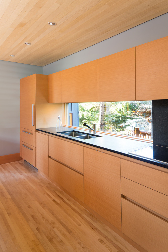 Huge minimalist l-shaped light wood floor and beige floor open concept kitchen photo in Vancouver with flat-panel cabinets, granite countertops, black backsplash, an island, a drop-in sink, light wood cabinets, window backsplash, black appliances and black countertops