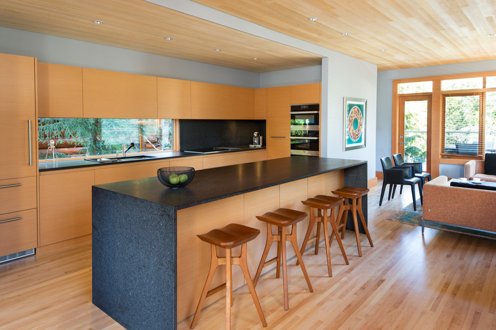 Example of a huge minimalist l-shaped light wood floor and beige floor open concept kitchen design in Vancouver with flat-panel cabinets, granite countertops, an island, window backsplash, black appliances, a drop-in sink, light wood cabinets, black backsplash and black countertops