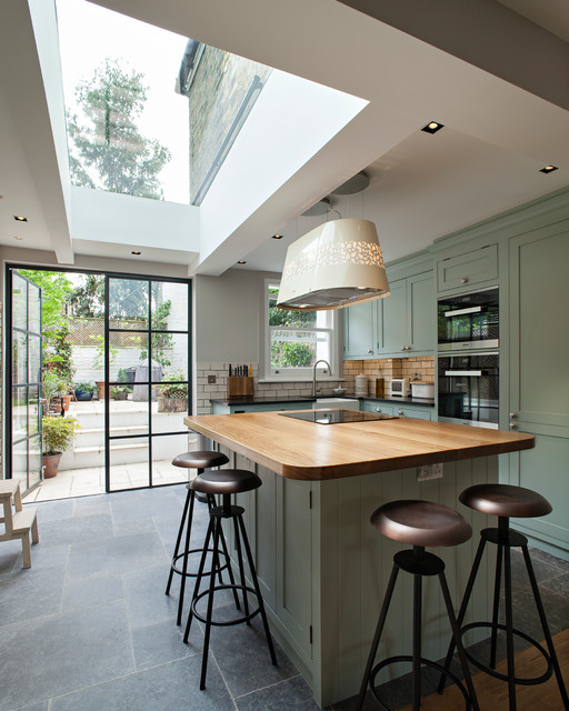 Medium sized contemporary l-shaped kitchen in London with a belfast sink, shaker cabinets, green cabinets, wood worktops, white splashback, metro tiled splashback, black appliances, ceramic flooring and an island.
