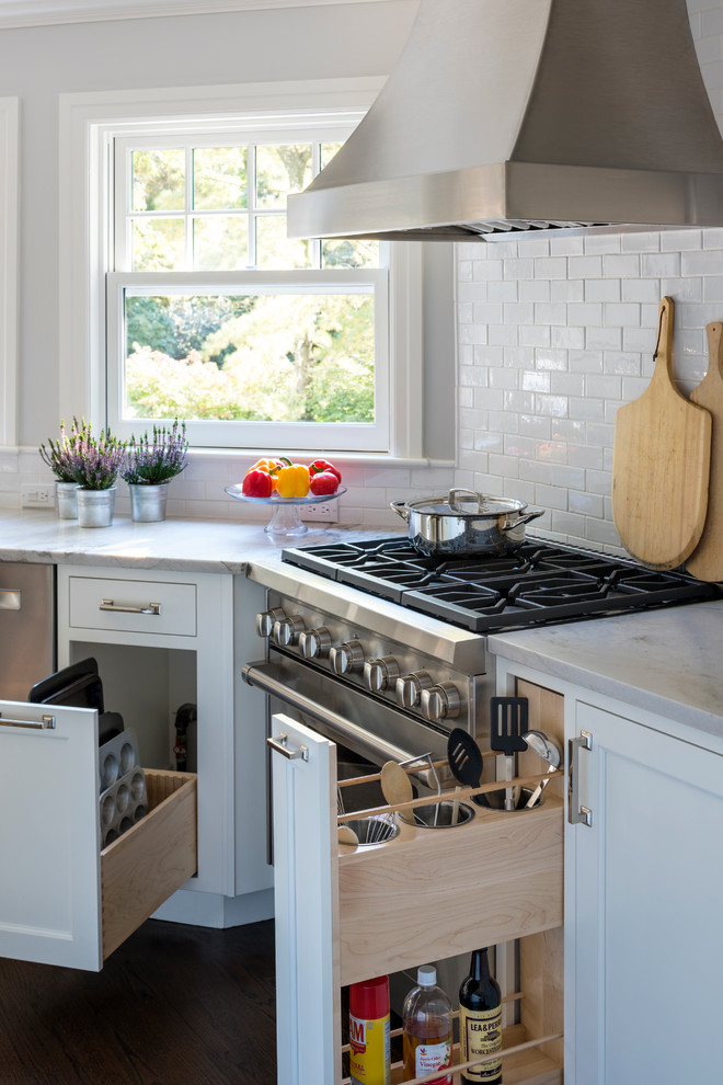 Inspiration for a mid-sized transitional l-shaped dark wood floor eat-in kitchen remodel in New York with an undermount sink, shaker cabinets, white cabinets, quartzite countertops, white backsplash, ceramic backsplash, stainless steel appliances and an island