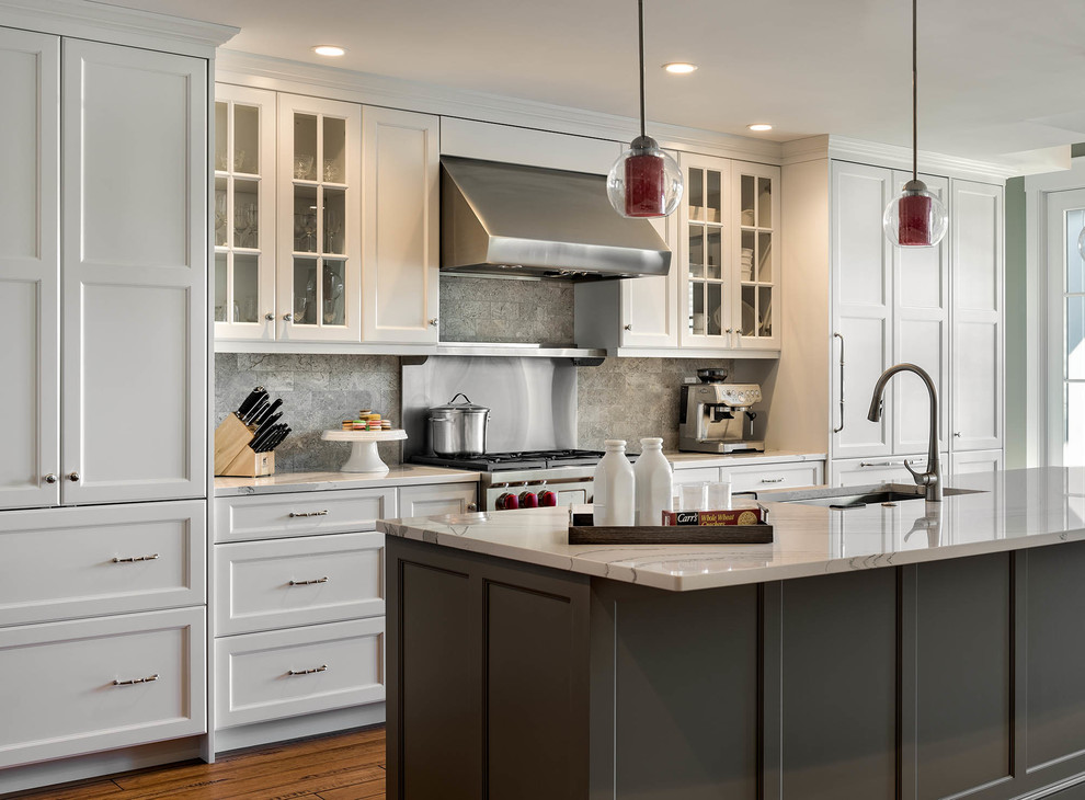 Inspiration for a large transitional galley medium tone wood floor eat-in kitchen remodel in Boston with an undermount sink, shaker cabinets, white cabinets, gray backsplash, stainless steel appliances, an island, quartz countertops and limestone backsplash