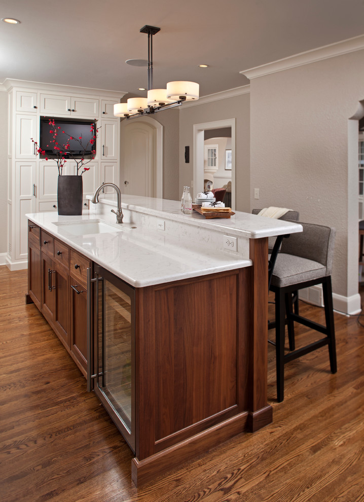 Inspiration for a mid-sized transitional galley dark wood floor kitchen remodel in Minneapolis with dark wood cabinets, an undermount sink, beaded inset cabinets, quartz countertops and an island