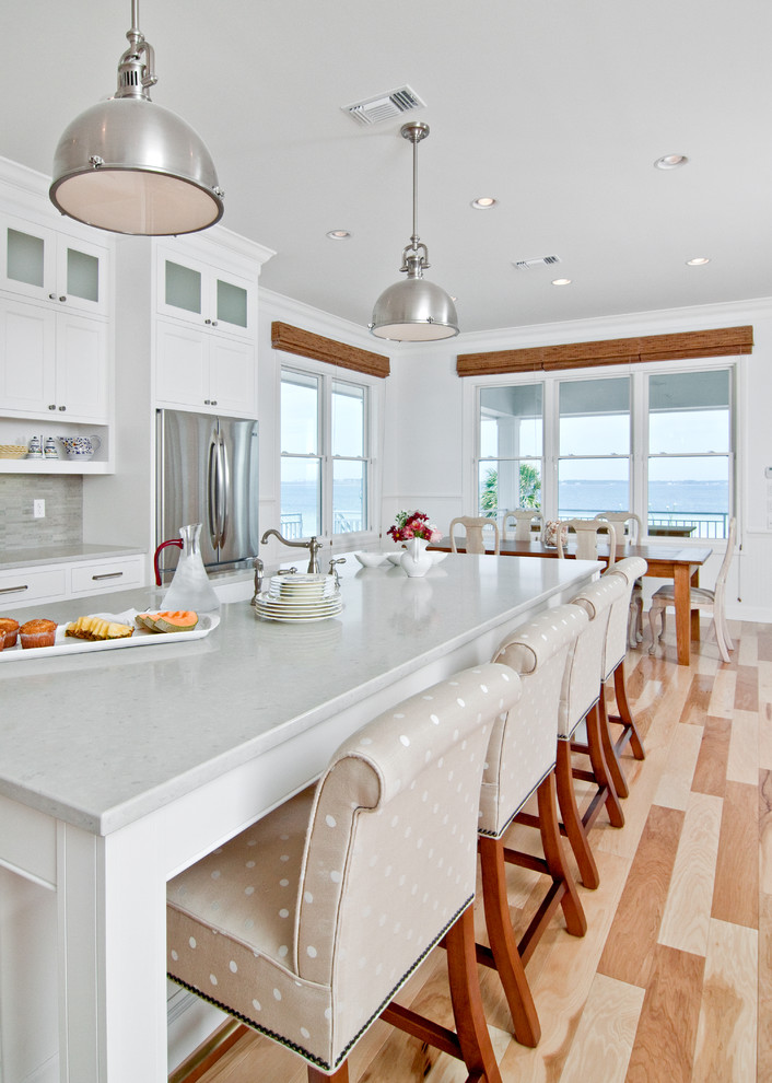 Inspiration for a timeless eat-in kitchen remodel in Other with quartz countertops, white cabinets, stainless steel appliances and gray backsplash