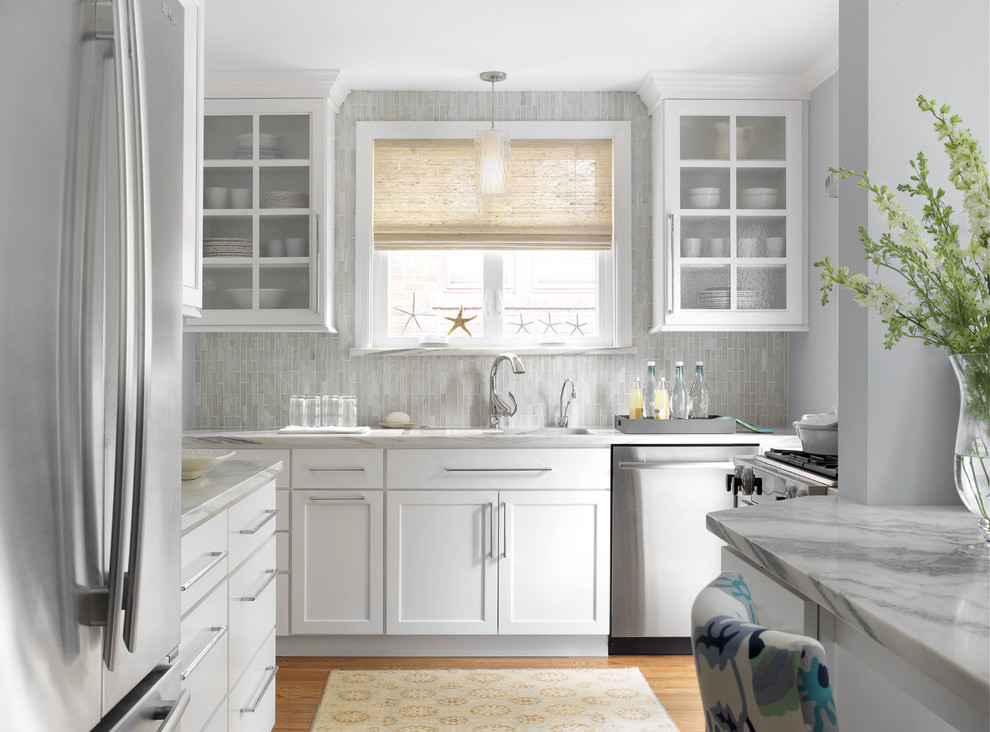 Inspiration for a coastal medium tone wood floor kitchen remodel in St Louis with an undermount sink, shaker cabinets, white cabinets, gray backsplash, stainless steel appliances, marble countertops and matchstick tile backsplash