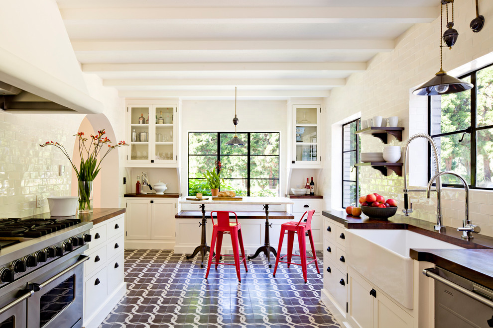 Inspiration for a mediterranean galley enclosed kitchen remodel in Portland with a farmhouse sink, shaker cabinets, white cabinets, wood countertops, white backsplash, subway tile backsplash and stainless steel appliances