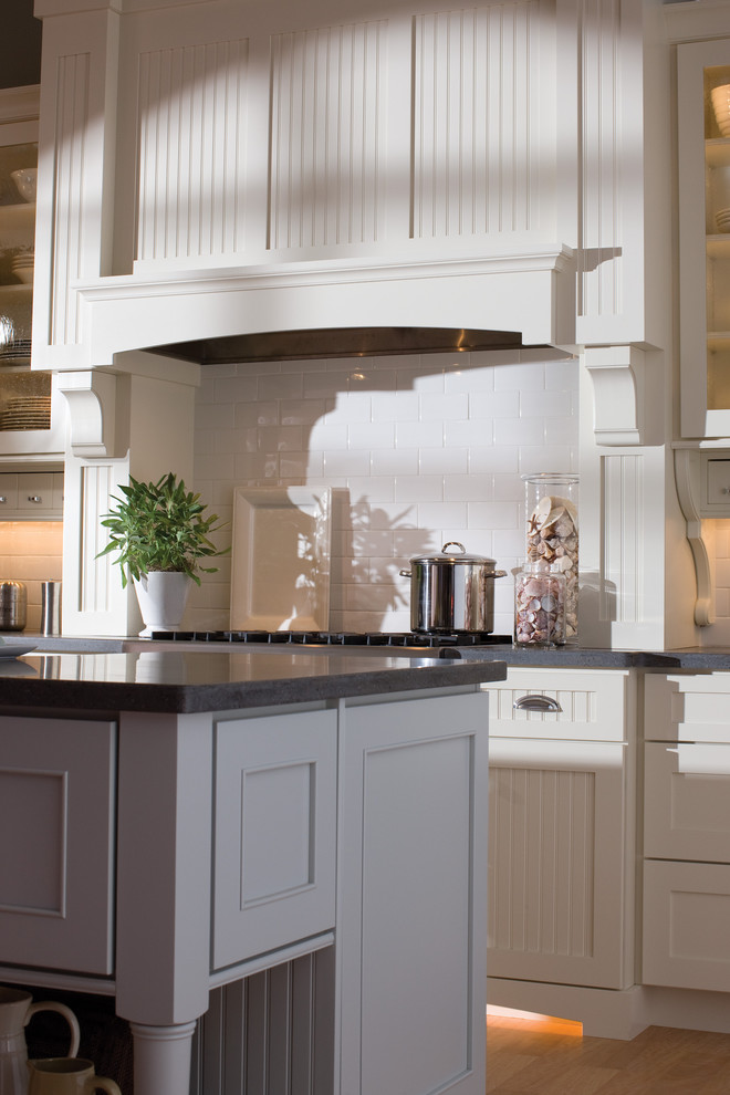 Inspiration for an eclectic light wood floor kitchen remodel in Minneapolis with a farmhouse sink, flat-panel cabinets, white cabinets, solid surface countertops, white backsplash, subway tile backsplash, stainless steel appliances and an island