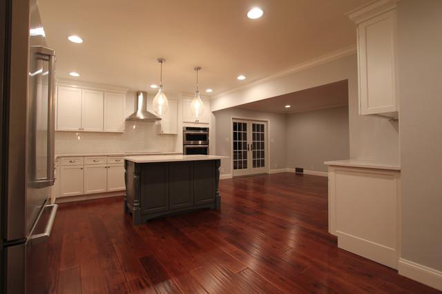 White farmhouse kitchen with black island and dark wood flooring farmhouse-kitchen