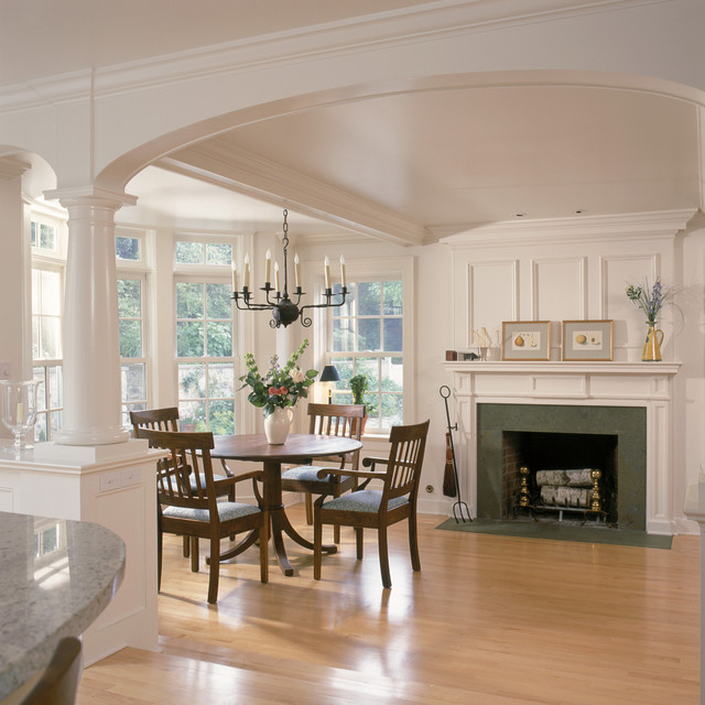 White kitchen and breakfast room with fireplace and arches for Dining room fireplace ideas