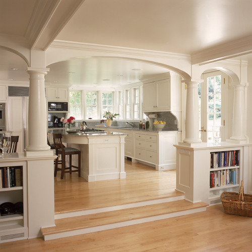 White kitchen and breakfast room with fireplace and arches