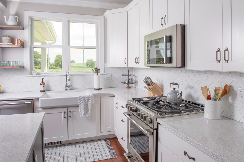 Inspiration for a mid-sized transitional l-shaped medium tone wood floor and brown floor open concept kitchen remodel in Other with a farmhouse sink, shaker cabinets, white cabinets, white backsplash, paneled appliances, an island, quartzite countertops and subway tile backsplash