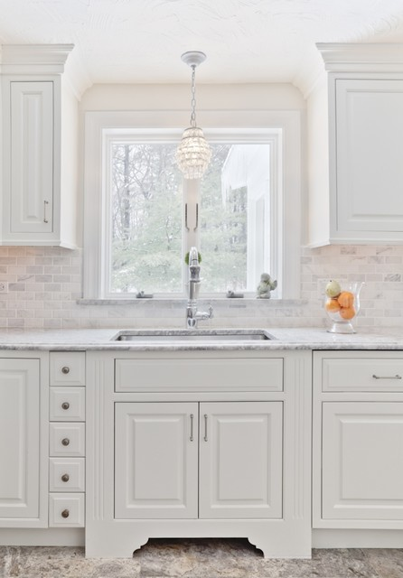 Inspiration for a timeless kitchen remodel in Boston with a single-bowl sink, raised-panel cabinets, white cabinets, white backsplash and marble backsplash