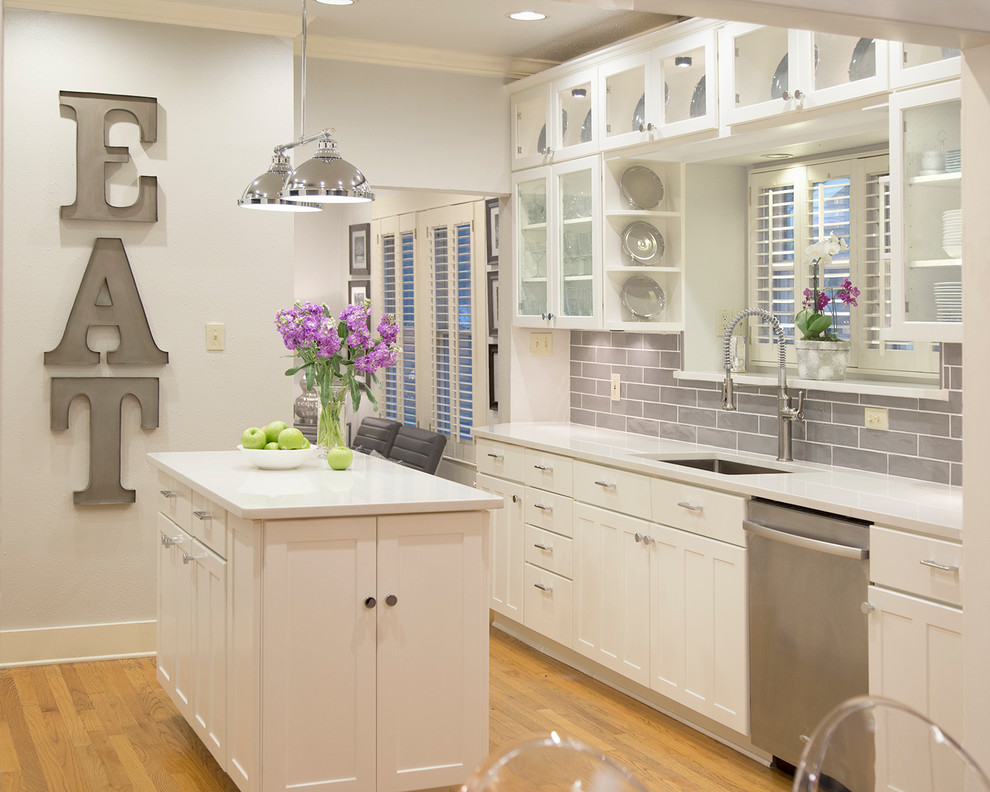 Kitchen - mid-sized transitional light wood floor and brown floor kitchen idea in Austin with an undermount sink, recessed-panel cabinets, white cabinets, quartz countertops, gray backsplash, ceramic backsplash, stainless steel appliances and an island