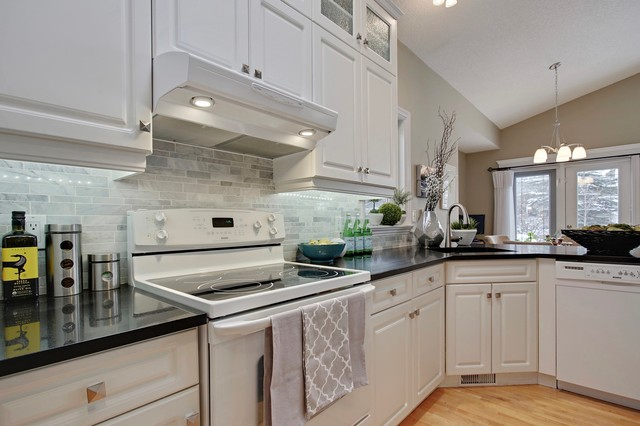 Inspiration for a small timeless u-shaped light wood floor kitchen pantry remodel in Calgary with an integrated sink, raised-panel cabinets, white cabinets, quartz countertops, gray backsplash, white appliances, an island and stone tile backsplash