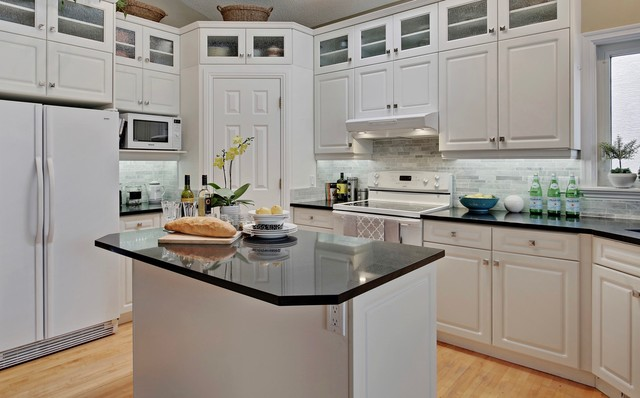 Small elegant u-shaped light wood floor kitchen pantry photo in Calgary with an integrated sink, raised-panel cabinets, white cabinets, quartz countertops, gray backsplash, white appliances, an island and stone tile backsplash