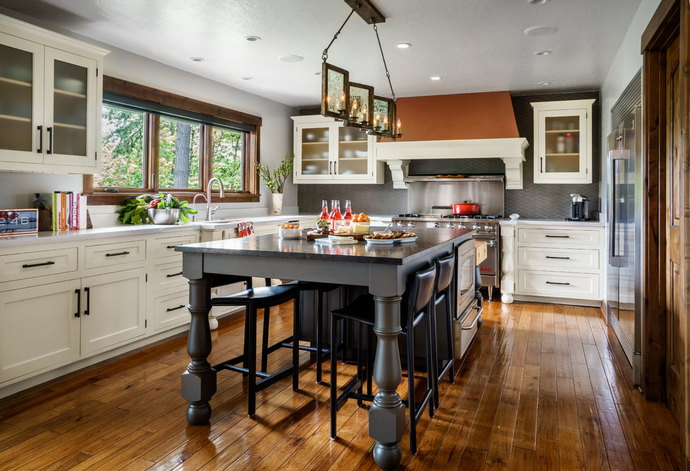 Large elegant u-shaped medium tone wood floor and brown floor kitchen photo in Portland with an undermount sink, white cabinets, quartz countertops, gray backsplash, glass tile backsplash, stainless steel appliances, an island and shaker cabinets