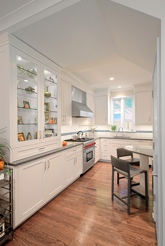 Eat-in kitchen - mid-sized transitional l-shaped medium tone wood floor eat-in kitchen idea in Chicago with an undermount sink, shaker cabinets, white cabinets, white backsplash, subway tile backsplash, stainless steel appliances and an island