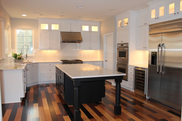 white kitchen with black island, multi-colored bamboo flooring contemporary- kitchen