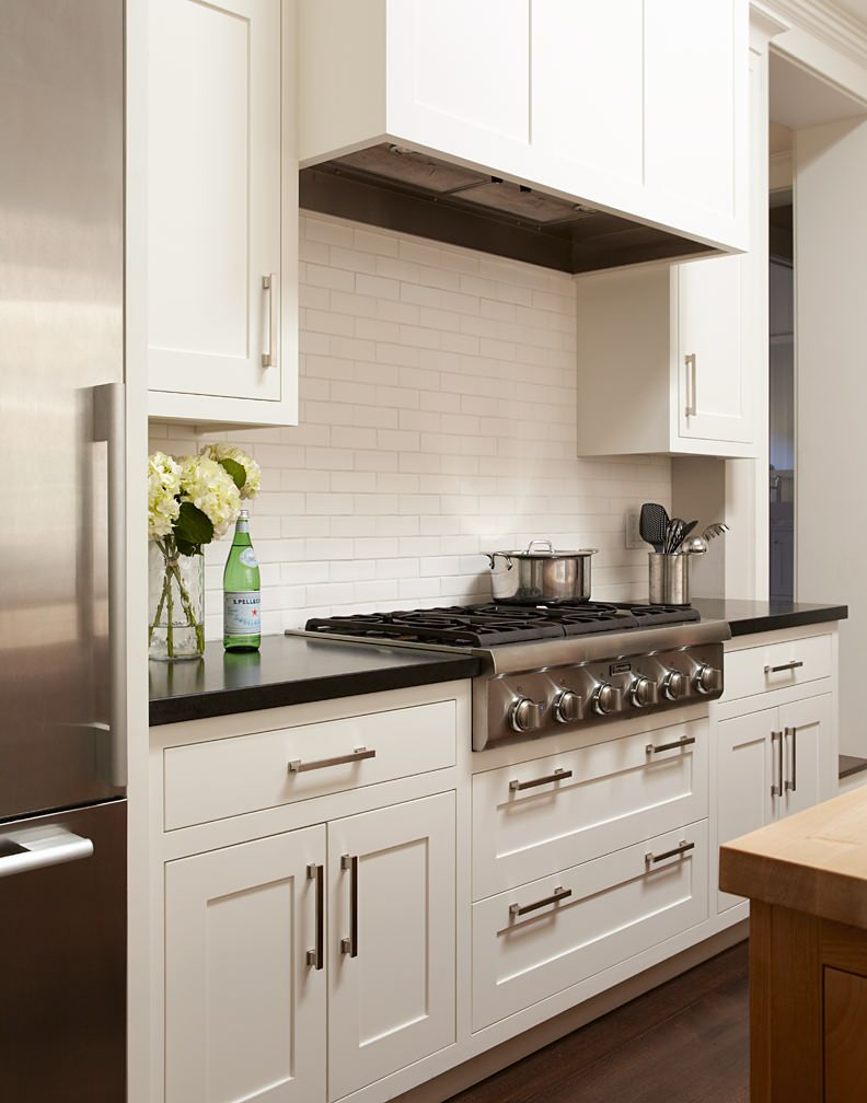 White kitchen with cooktop and hood