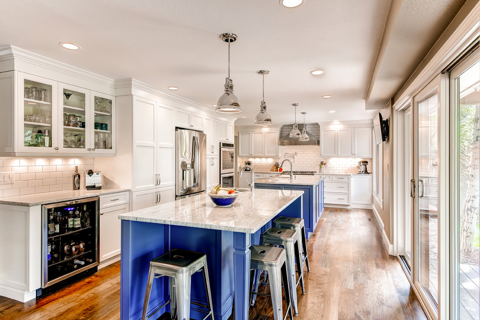 Inspiration for a large transitional l-shaped eat-in kitchen remodel in Denver with a farmhouse sink, shaker cabinets, blue cabinets, white backsplash, subway tile backsplash, stainless steel appliances and two islands