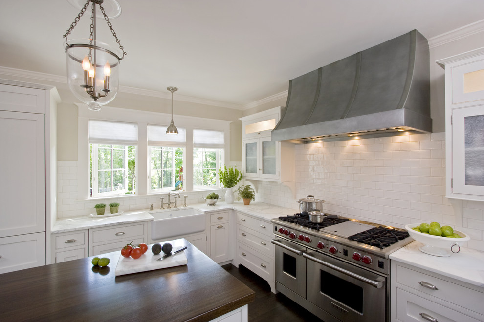 Large elegant u-shaped dark wood floor eat-in kitchen photo in New York with a farmhouse sink, wood countertops, beaded inset cabinets, white cabinets, white backsplash, ceramic backsplash, an island and stainless steel appliances