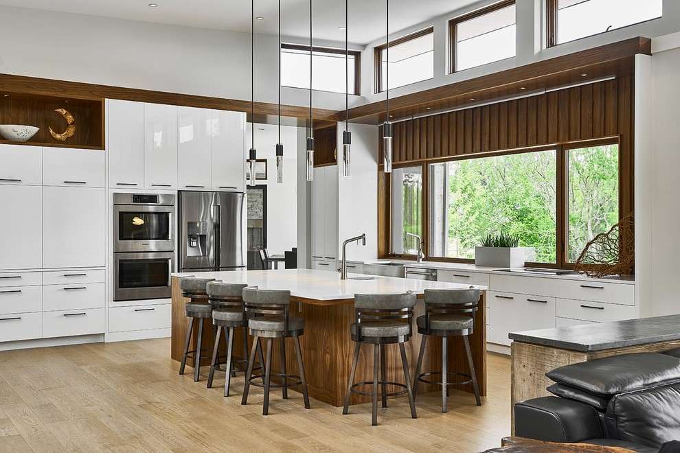 Large trendy l-shaped light wood floor and beige floor open concept kitchen photo in Other with flat-panel cabinets, white cabinets, quartz countertops, stainless steel appliances, an island, a farmhouse sink, window backsplash and white countertops
