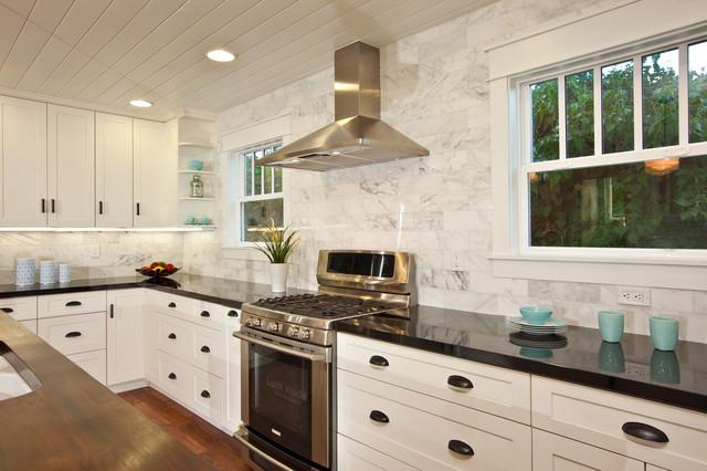White Kitchen with wood island, carrara backsplash, black granite