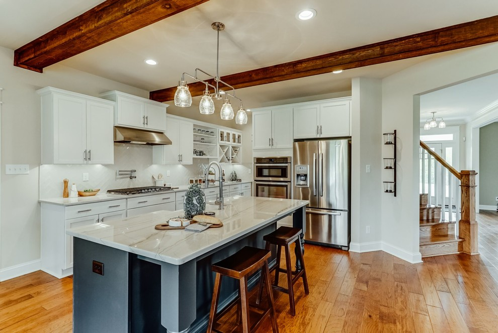 Open concept kitchen - mid-sized contemporary l-shaped medium tone wood floor and brown floor open concept kitchen idea in Richmond with a farmhouse sink, shaker cabinets, white cabinets, quartzite countertops, white backsplash, subway tile backsplash, stainless steel appliances and an island