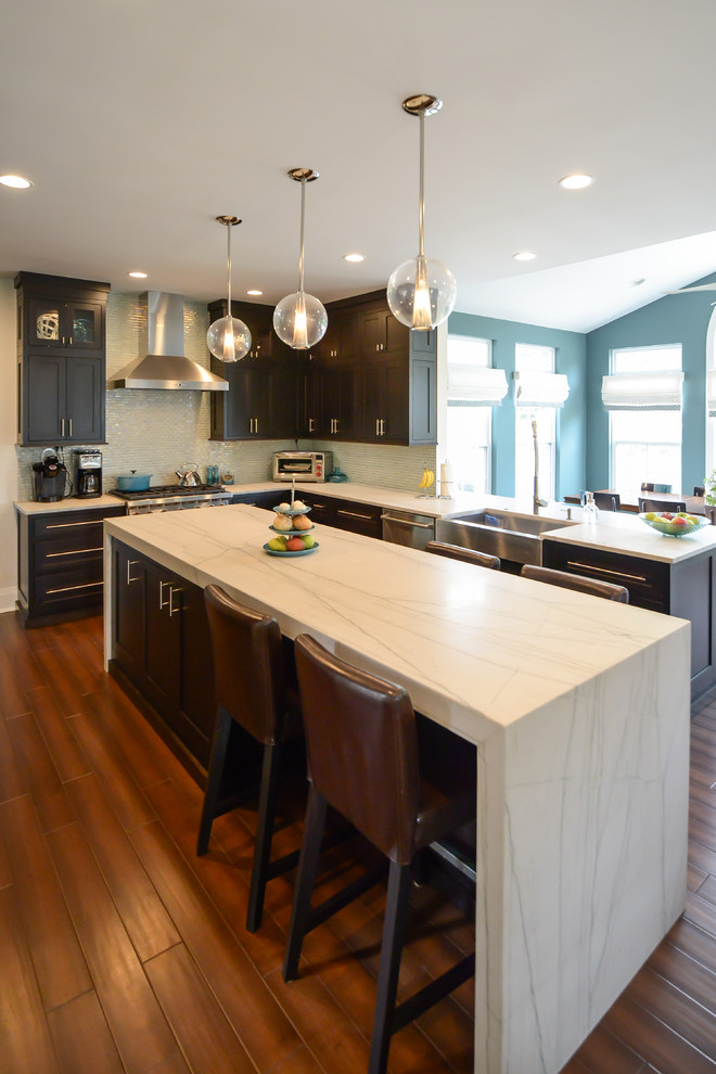Example of a mid-sized trendy l-shaped medium tone wood floor eat-in kitchen design in Philadelphia with a farmhouse sink, shaker cabinets, dark wood cabinets, quartzite countertops, glass tile backsplash, stainless steel appliances and an island