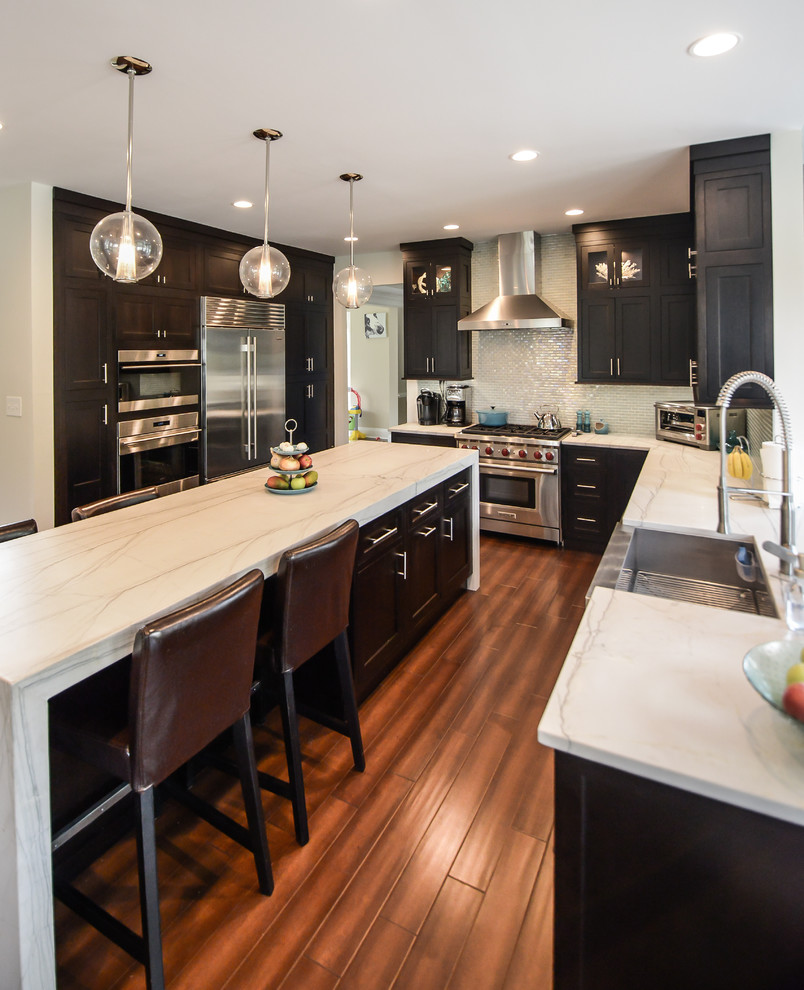 Eat-in kitchen - mid-sized contemporary l-shaped medium tone wood floor eat-in kitchen idea in Philadelphia with a farmhouse sink, shaker cabinets, dark wood cabinets, quartzite countertops, glass tile backsplash, stainless steel appliances and an island