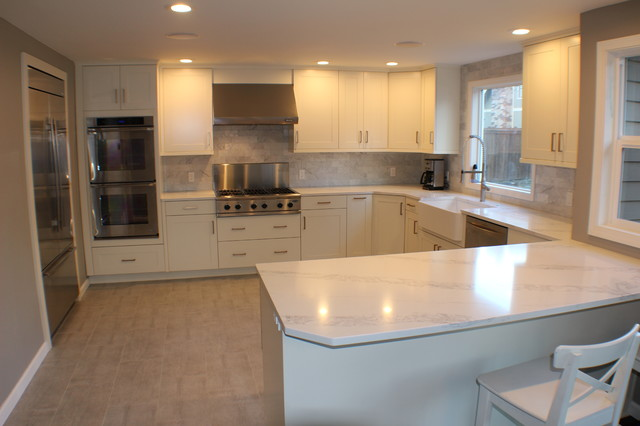 Example of a mid-sized classic u-shaped beige floor enclosed kitchen design in Other with a farmhouse sink, shaker cabinets, white cabinets, marble countertops, gray backsplash, marble backsplash, stainless steel appliances, a peninsula and white countertops