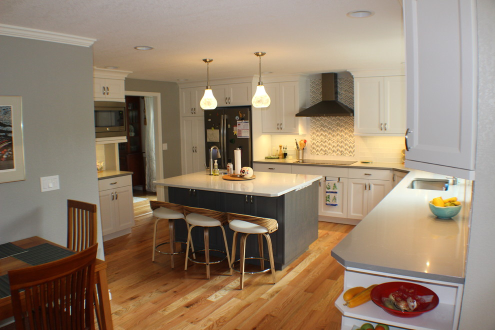 Inspiration for a mid-sized transitional l-shaped medium tone wood floor and brown floor eat-in kitchen remodel in Other with an undermount sink, shaker cabinets, white cabinets, quartz countertops, white backsplash, stainless steel appliances, an island and gray countertops