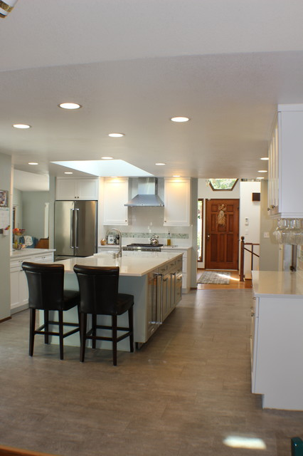 Large transitional single-wall eat-in kitchen photo in Other with a farmhouse sink, shaker cabinets, white cabinets, white backsplash, stainless steel appliances, an island and white countertops