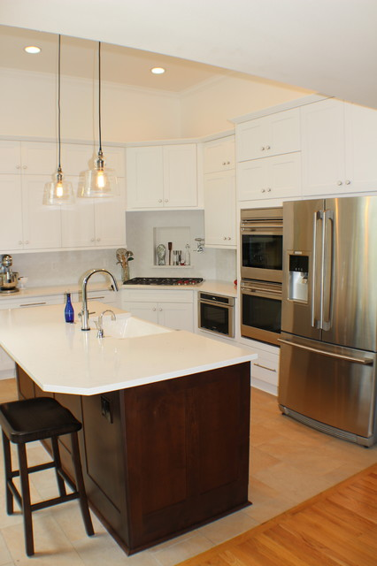 Mid-sized transitional l-shaped porcelain floor and beige floor enclosed kitchen photo in Other with a farmhouse sink, shaker cabinets, white cabinets, solid surface countertops, white backsplash, stainless steel appliances, an island and white countertops